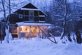 Wooden house in dark winter forest — Stock Photo