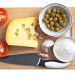 Wooden board with cheese,tomatoes,olives and garlic — Stock Photo