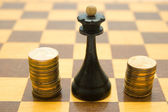 Chess queen and coins on chessboard — Stock Photo