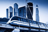 Skyscrapers and monorail train. Blue toned image — Stock Photo