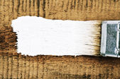 Paint brush with white paint stroke on wooden background  — Stock Photo