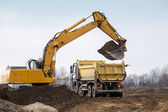Digger loading trucks with soil — Stockfoto