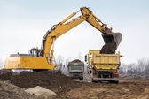Digger loading trucks with soil — Стоковое фото