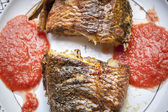 Baked tilapia served with red pepper sauce — Stock Photo