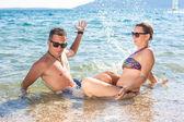 Smiling couple enjoying in water — Стоковое фото