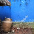 Weathered blue wall with large clay pot — Stock Photo #28443351