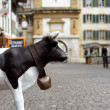 Spotty black and whitet plastic cow on the european streen — Stock Photo