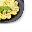 Tortellini on black plate — Stock Photo