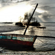 Red White Blue Dhow Sailing boat stranded at low tide in ocean M — Stock Photo