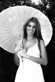 Smiling Blond lady holding umbrella — Stock Photo