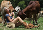 Beautiful lady with the cows — Stock Photo