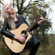 Blonde lady playing guitar and signing in the forest — Stock Photo