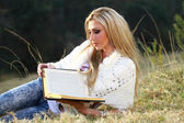 Blonde lady reading Bible — Stock Photo