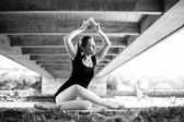 Balerina sitting under bridge looking over her shoulder — Stock Photo