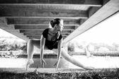 Blonde Ballerina standing under a bridge — Stock Photo
