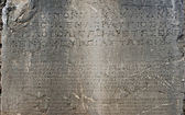 Ancient Greek script carved on stone plate, Delphi, Greece — Foto de Stock