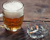 Pint of Beer and a lit cigarett — Stock Photo