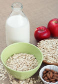 Bowl of oatmeal with apples almonds and milk — Stockfoto