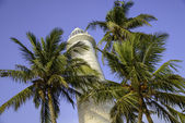 Old lighthouse on a background of blue sky is surrounded by palm — Stock Photo