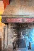 Ancient castle fireplace made of stone and brick. — Stockfoto
