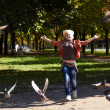 Running a young girl and a flight of birds — Stock Photo