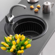 Granite kitchen sink with mixer tap, yellow tulips in the foreground and a cup of coffee in the background — Stock Photo