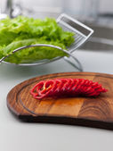 Sliced red peppers on a cutting board with green lettuce on the background — Stock Photo