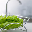 Green lettuce with blurred tap on background — Stock Photo #24341133