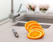 Sliced orange and knife on kitchen sink — Stock Photo