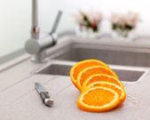Sliced orange and knife on kitchen sink — Stock Photo