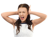 Young woman trying to block out a noise with her hands — Stock Photo