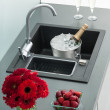 Granite kitchen sink with mixer tap, red flowers and strawberrie — Stock Photo #24353873
