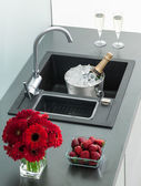 Granite kitchen sink with mixer tap, red flowers and strawberrie — Stock Photo