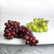 Red and white bunches of grapes on white table. — Stock Photo