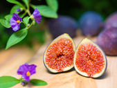 Fresh sliced figs on the wooden table and purple flowers in fore — Stock Photo