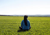 Girl sitting on the field — Stock Photo