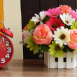 Alarm clock on table with flower — Stock Photo