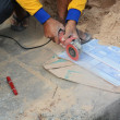 Stock Photo: Grinder worker cuts stone electric tool worker is tiling a