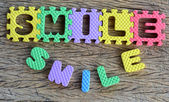 Jigsaw written smile word on wood background — Stock Photo