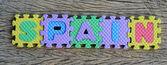 Jigsaw written Spain word on wood background — Stockfoto