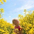 Happy toddler girl in rape seed field — Stock Photo