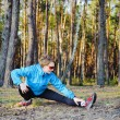Fit young woman stretching in the forest — Stock Photo