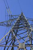 High voltage transmission pylon on blue sky background — Stock fotografie