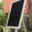 Empty black board (menu board) at a restaurant — Stock Photo