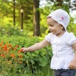 Little girl playing with flowers — Stock Photo