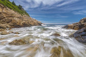 Ocean waves crashing against a rocky shore- slow shutterspeed — Stock Photo