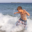 Stock Photo: Boy running through the water at the beach