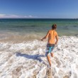 Boy running through the water at the beach — Stock Photo