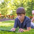 Boy using his laptop outdoor in park — Stock Photo