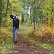 Photographer in autumn forest — Stock Photo #26722941